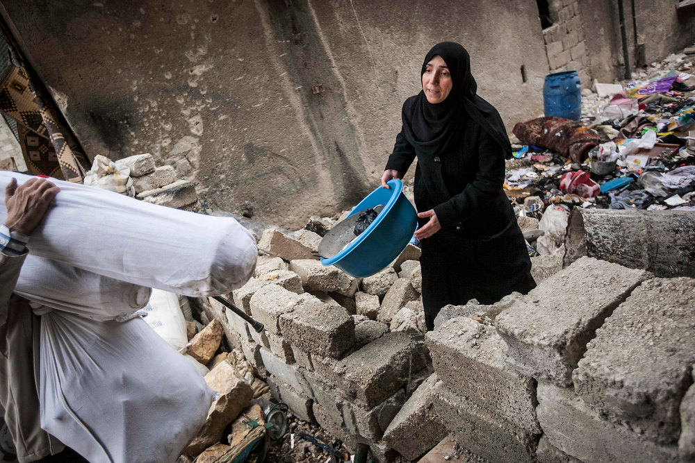 Description of . In this Tuesday, Dec. 11, 2012 photo, a Syrian woman collects her belongings from rubble after her home was damaged due to fighting between Free Syrian Army fighters and government forces in Aleppo, Syria. (AP Photo/Narciso Contreras)
