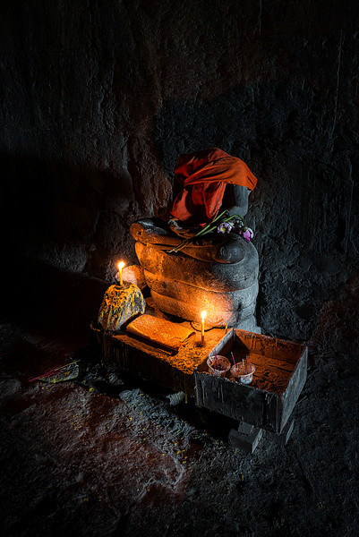 Original beheaded Buddha with prayer offerings at Angkor Wat Siem Reap, Cambodia