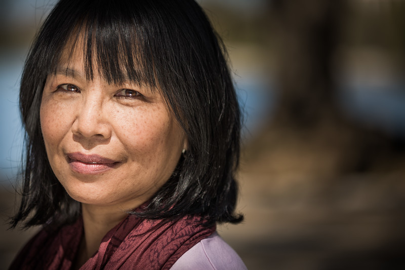 Headshot of an Asian woman in a park.