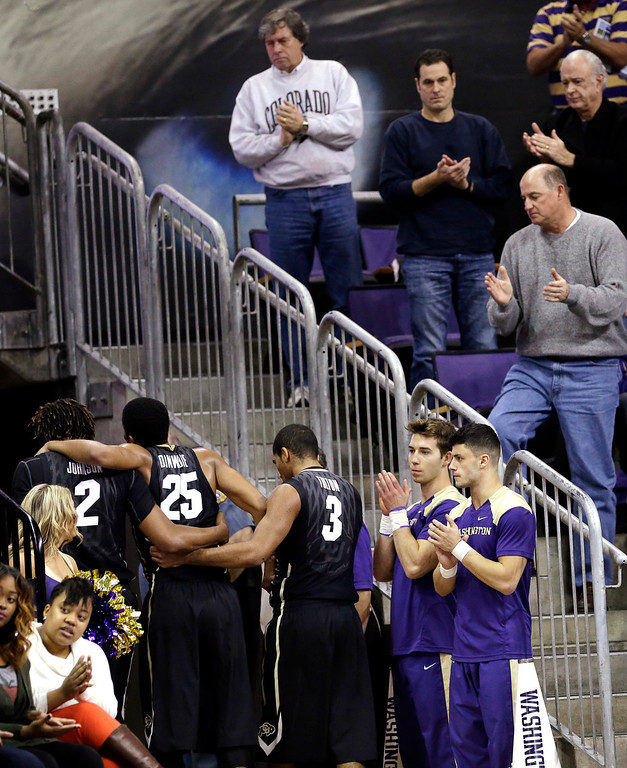 . Fans and cheerleaders cheer Colorado\'s Spencer Dinwiddie (25) as he is assisted from the court after being injured against Washington in the first half of an NCAA college basketball game on Sunday, Jan. 12, 2014, in Seattle. (AP Photo/Elaine Thompson)