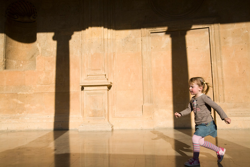 Little girl running on the upper gallery of the Palace of Charles V, Granada, Spain