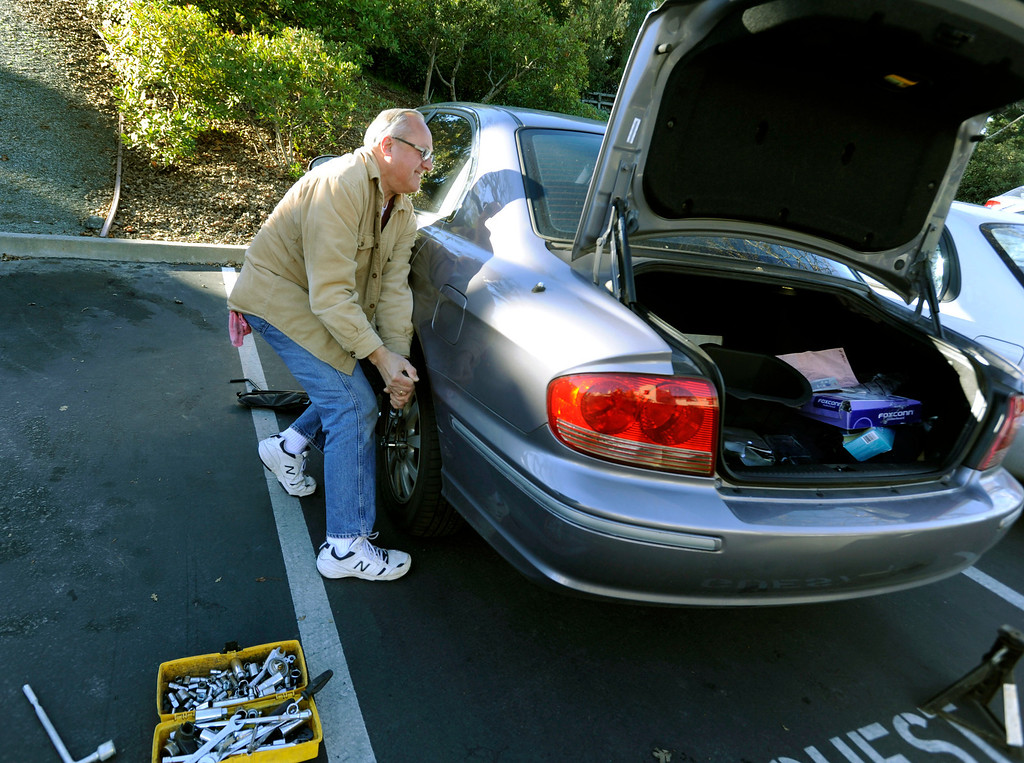 . Dan Zywicki, of Concord, helps remove the first of four flat tires on his daughter\'s car along Bel Air Drive in Concord, Calif., on Monday, Feb. 11, 2013. Zywicki said his daughter, Kay Zywicki, discovered the flats on Sunday. Concord police reported that tiresd were slashed on about 60 vehicles in the area. (Susan Tripp Pollard/Staff)