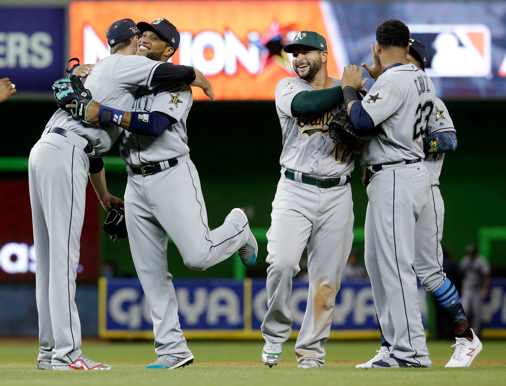 . American League\'s Seattle Mariners Robinson Cano (22), second from left, is hugged by Cleveland Indians pitcher Andrew Miller, after winning the MLB baseball All-Star Game, Tuesday, July 11, 2017, in Miami. Cano hit a home run in the tenth inning to win the game. The American League defeated the National league 2-1. (AP Photo/Lynne Sladky)