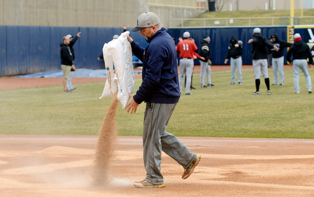 . Maribeth Joeright/MJoeright@News-Herald.com<p> As members of the Lansing Lugnuts warm up, Captains head grounds keeper Dan Stricko pours a drying agent on the infield in preparation for the home opener at Classic Park, April 4, 2014.