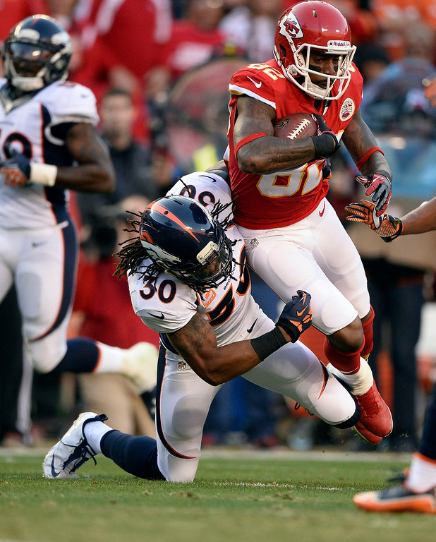 . Kansas City Chiefs wide receiver Dwayne Bowe (82) is brought down by Denver Broncos strong safety David Bruton (30) after a short gain during the first quarter December 1, 2013 at Arrowhead Stadium.  (Photo by John Leyba/The Denver Post)