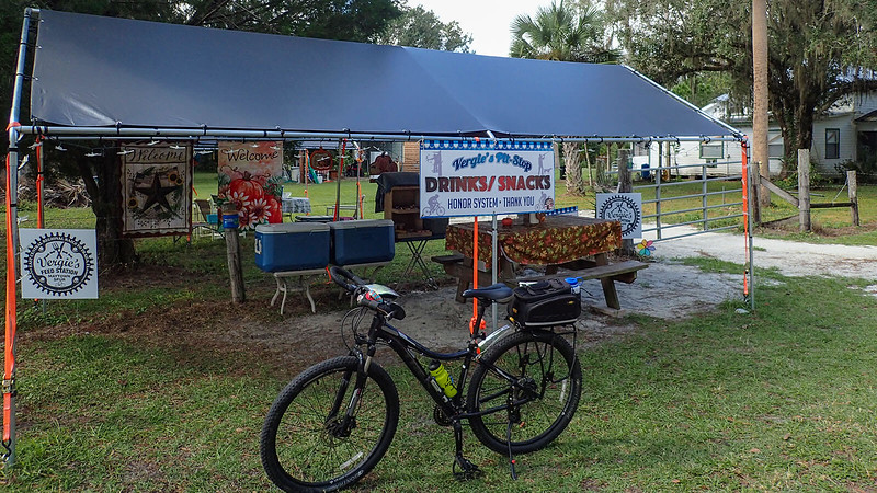Bike in front of canopied picnic table with snacks