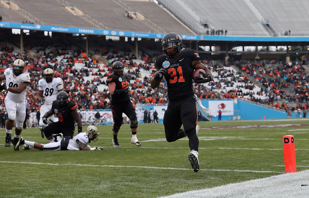 Description of . Jeremy Smith #31 of the Oklahoma State Cowboys runs for a touchdown against the Purdue Boilermakers during the Heart of Dallas Bowl at Cotton Bowl on January 1, 2013 in Dallas, Texas.  (Photo by Ronald Martinez/Getty Images)