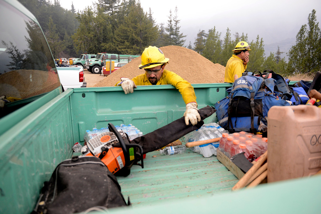 . Sequoia National Forest firefighter Rigoberto Bedolla grabs his chainsaw at Highway 1 and Pfeiffer Ridge Road in Big Sur, Calif. on Wednesday December 18, 2013. (Photo David Royal/ Monterey County Herald)