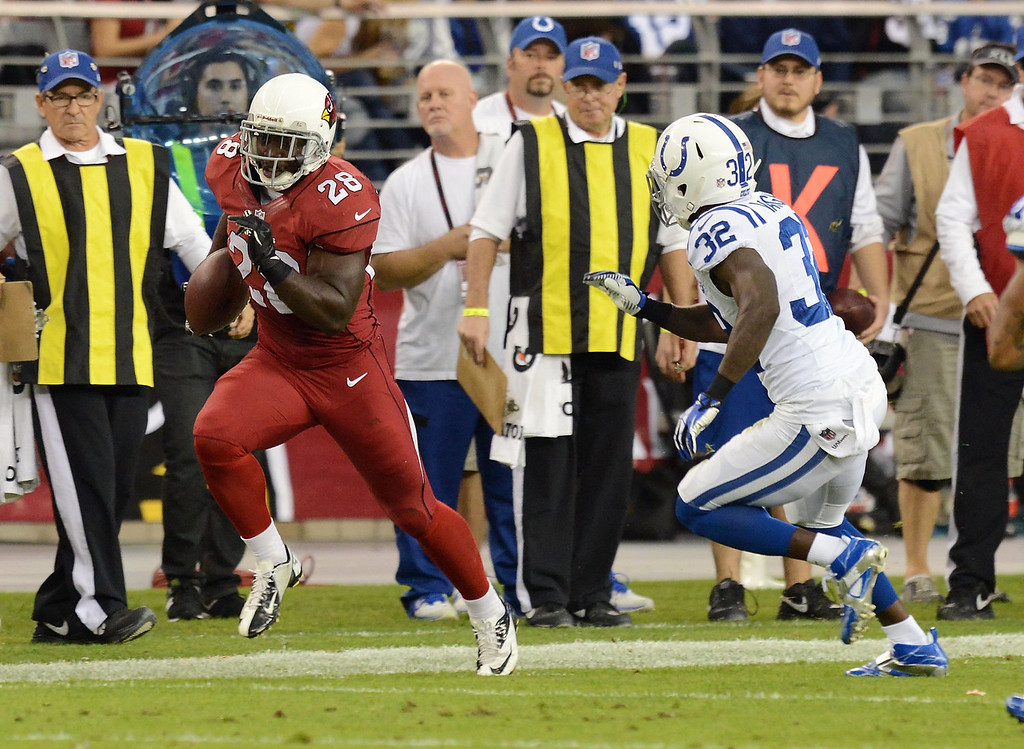. Rashard Mendenhall #28 of the Arizona Cardinals runs down the sideline with the ball while being chased by Cassius Vaughn #32 of the Indianapolis Colts at University of Phoenix Stadium on November 24, 2013 in Glendale, Arizona.  (Photo by Norm Hall/Getty Images)