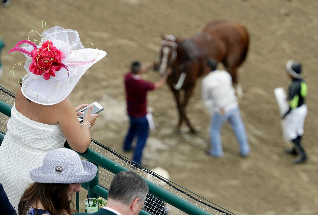 . A fan watches a horse get ready for a race before the 142nd running of the Kentucky Derby horse race at Churchill Downs Saturday, May 7, 2016, in Louisville, Ky. (AP Photo/Charlie Riedel)
