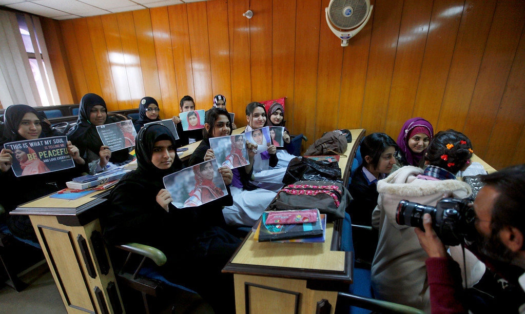 . A Pakistani photographer takes a picture of students showing pictures of Nobel Peace Prize winner Malala Yousafzai during a ceremony at their school in Islamabad, Pakistan, Wednesday, Dec. 10, 2014. The 17-year-old Malala of Pakistan and the 60-year-old Kailash Satyarthi of India on Wednesday received the Nobel Peace Prize for risking their lives to fight for children\'s rights. (AP Photo/Anjum Naveed)