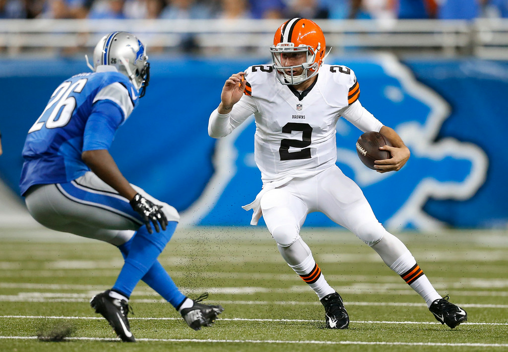 . Cleveland Browns quarterback Johnny Manziel (2) scrambles from Detroit Lions strong safety Don Carey (26) in the first half of a preseason NFL football game at Ford Field in Detroit, Saturday, Aug. 9, 2014.  (AP Photo/Rick Osentoski)