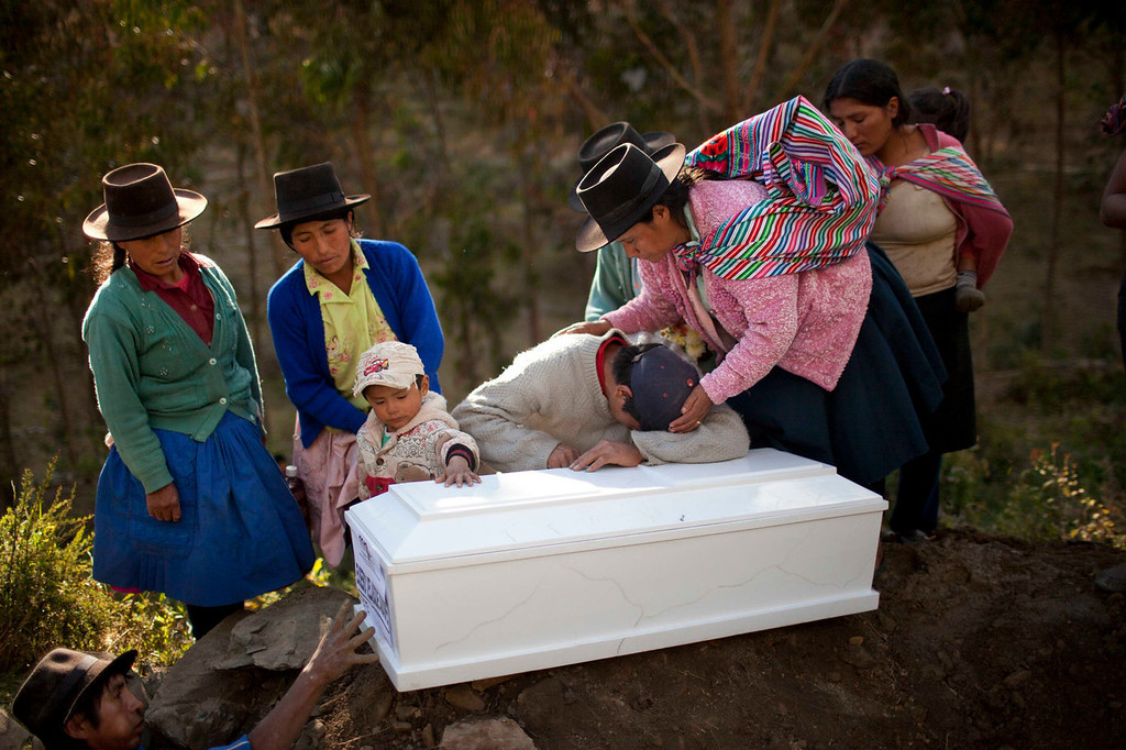 . Eusebio Velasque mourns over the coffin containing the remains of his father Edwin Velasque during a mass burial at the local cemetery in Chaca, Peru. Velasque is one of the Chaca residents tortured and killed on Jan. 8,1988 by Shining Path militants in retaliation for forming a self-defense committee. Their remains were exhumed in 2012 from a mass grave and released to family members on June 13, 2013.   (AP Photo/Rodrigo Abd)