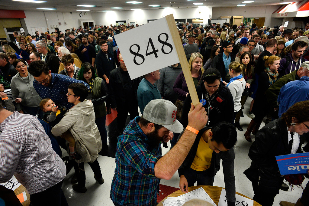 . Precinct coordinators hold up their numbered signs as hundreds of people gathered in the overflowing cafeteria during the caucus at East High school in Denver, Colorado on March 1, 2016. 18 precincts were represented at East High School and thousands of people turned out for the caucus. Organizers had anticipated about 20% of people from their precincts would turn out but many more actually came. (Photo by Helen H. Richardson/The Denver Post)