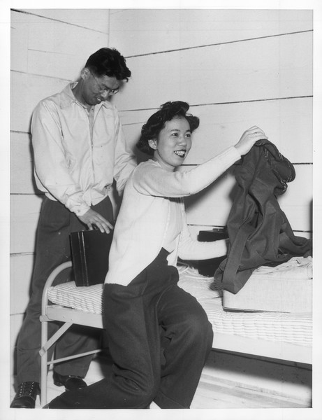 """""""First of San Francisco's Japanese to reach Tanforan was Mrs. Ichiro Iizuika -- Here she is shown with husband unpacking in their quarters.""""--caption on photograph"""