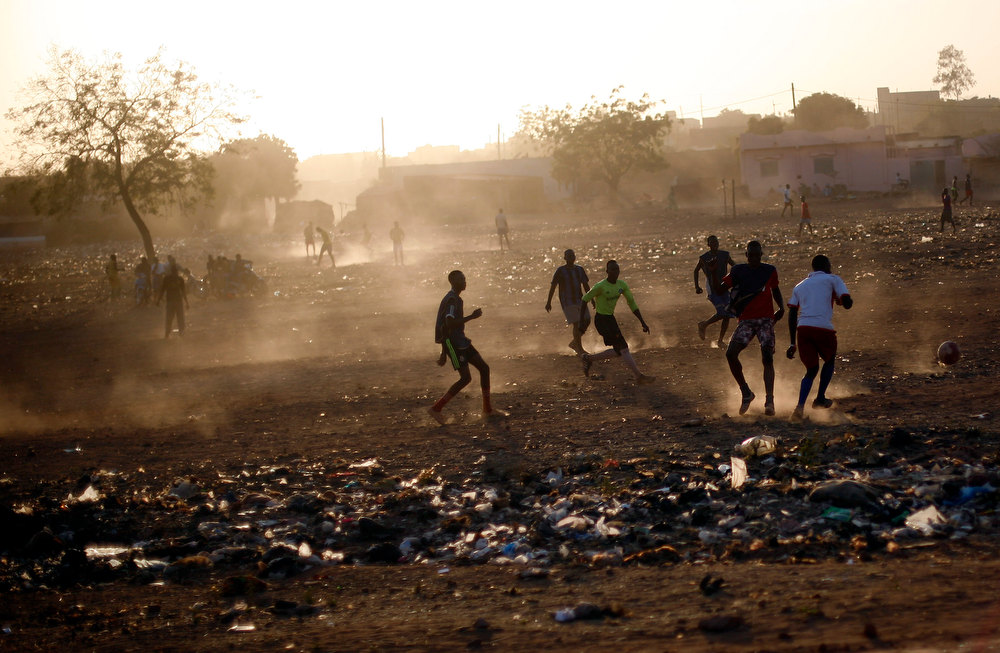 Description of . Young men play football in Bamako, Mali, Tuesday Jan. 15 2013. French forces led an all-night aerial bombing campaign Tuesday to wrest control of a small Malian town from armed Islamist extremists who seized the area, including its strategic military camp. A a convoy of 40 to 50 trucks carrying French troops crossed into Mali from Ivory Coast as France prepares for a possible land assault. Several thousand soldiers from the nations neighboring Mali are also expected to begin arriving in coming days. (AP Photo/Jerome Delay)