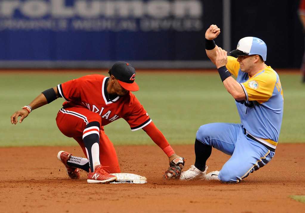 . Cleveland Indians shortstop Francisco Lindor tags out Tampa Bay Rays\' Corey Dickerson to complete a double play that started with a grounder to first by Lucas Duda during the first inning of a baseball game Saturday, Aug. 12, 2017, in St. Petersburg, Fla. Both teams are wearing throwback jerseys. (AP Photo/Steve Nesius)