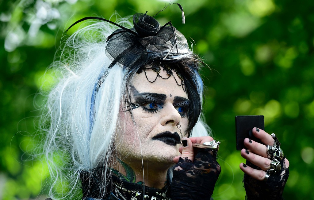 ". A man applies a black lipstick during a so-called ""Victorian Picnic\"" during the Wave-Gotik-Treffen (WGT) festival in Leipzig, eastern Germany, on May 13, 2016.   / AFP PHOTO / TOBIAS SCHWARZ/AFP/Getty Images"