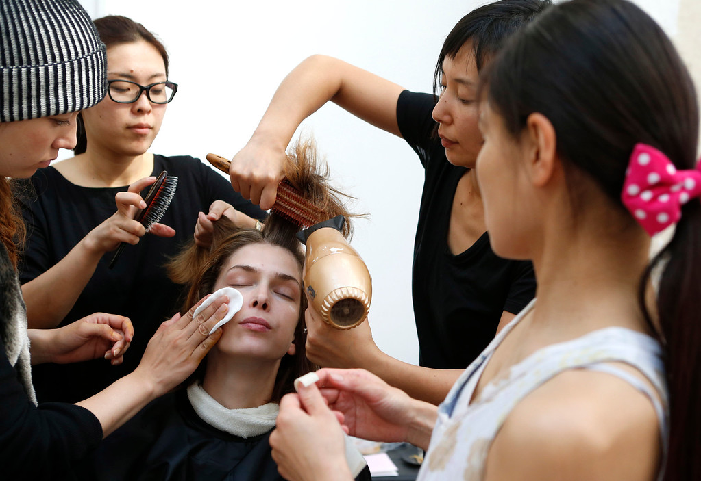 . A model is made up backstage before the presentation of Ground Zero\'s ready-to-wear Spring/Summer 2014 fashion collection, in Paris, Tuesday, Sept.24, 2013. (AP Photo/Jacques Brinon)