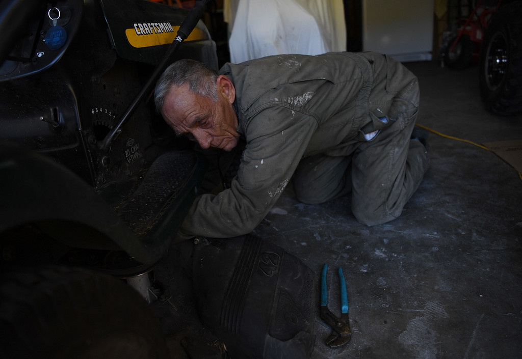 """. Somerset resident Mike Norton works on fixing his mower at his home in the small Colorado coal town, April 27, 2016. \""""The sad thing is, that it\'s not just the coal mines affected. It\'s all the businesses that are connected to it,\"""" said Norton. Two of the three major coal mines in the area recently closed. (Photo by RJ Sangosti/The Denver Post)"""