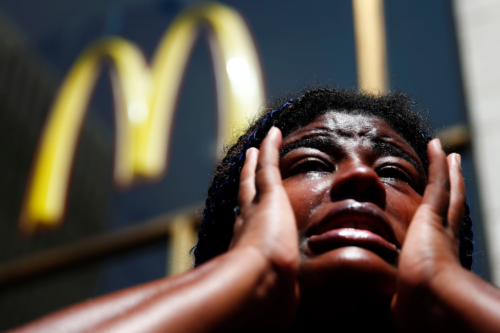 . Angela Owens, who works in the health care industry, wipes tears from her eyes as she speaks to members of the media at a protest to push fast-food chains to pay their employees at least $15 an hour, Thursday, Sept. 4, 2014, outside a McDonald\'s restaurant in Philadelphia. The protest movement, which is backed financially by the Service Employees International Union and others, has gained national attention at a time when the wage gap between the poor and the rich has become a hot political issue. (AP Photo/Matt Rourke)