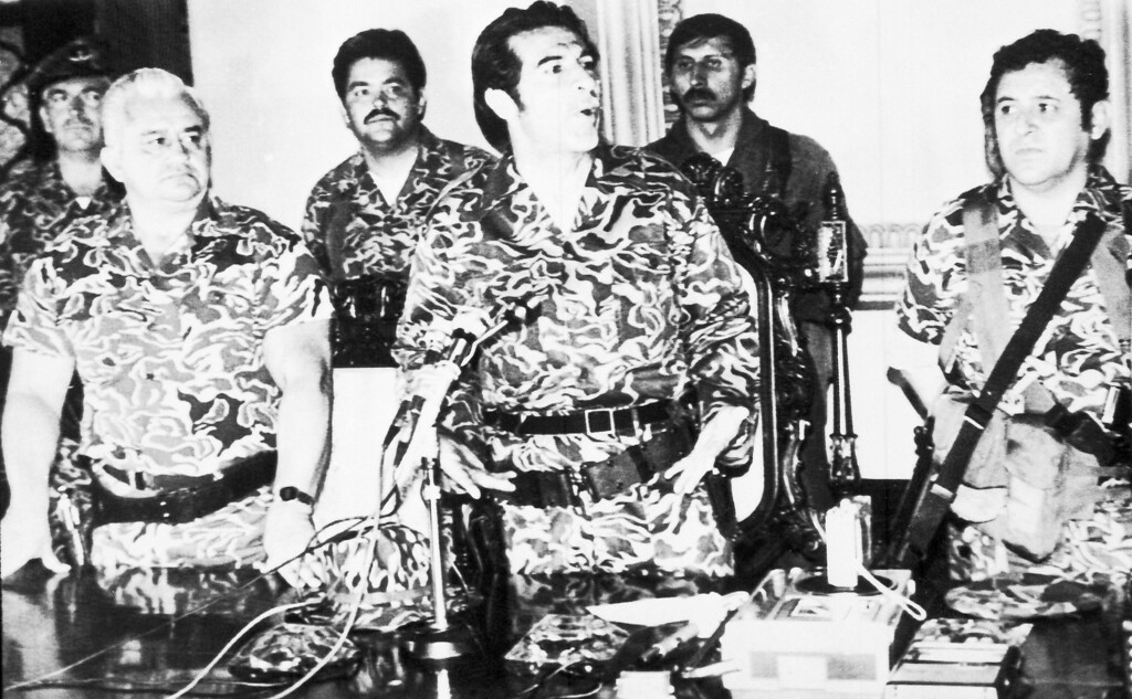 . FILE - In this March 23, 1982 photo, General Efrain Rios Montt, center, speaks at a press conference in Guatemala City, where he announced the formation of a junta in the aftermath of the overthrow of General Fernando Romeo Lucas Garcia\'s right wing government. At left is General Horacio Maldonado Shad and right is Colonel Luis Frandisco Gordillo. Rios Montt rose to power in this March 23, 1982 coup d\'etat, holding absolute power for just over a year before he himself was overthrown.  Rios Montt has ruled as Guatemalaís dictator, served as president of Congress, preached as an evangelical pastor and now, at 87, has become the first Latin American strongman to stand trial on genocide charges in his own country. (AP Photo, File)