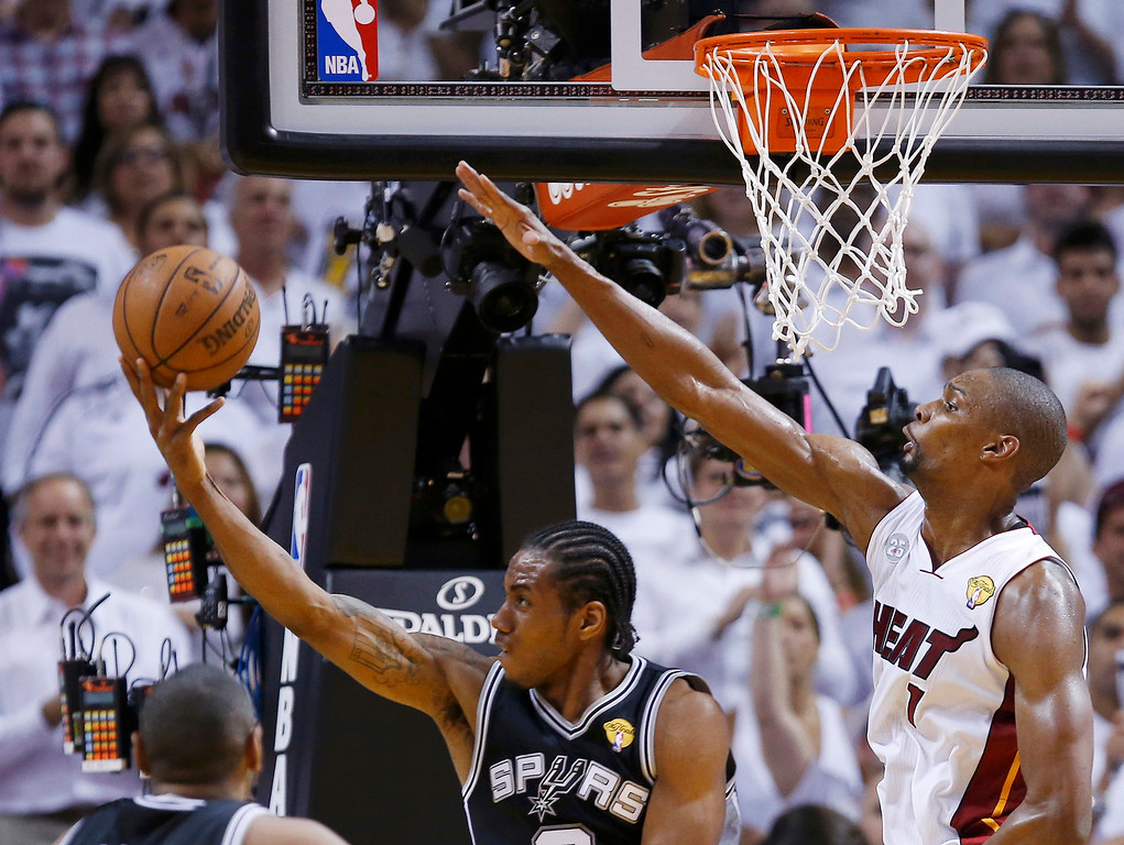 . San Antonio Spurs\' Kawhi Leonard (L) shoots for a basket and gets fouled by Miami Heat\'s Chris Bosh during the third quarter in Game 7 of their NBA Finals basketball playoff in Miami, Florida June 20, 2013. REUTERS/Mike Segar