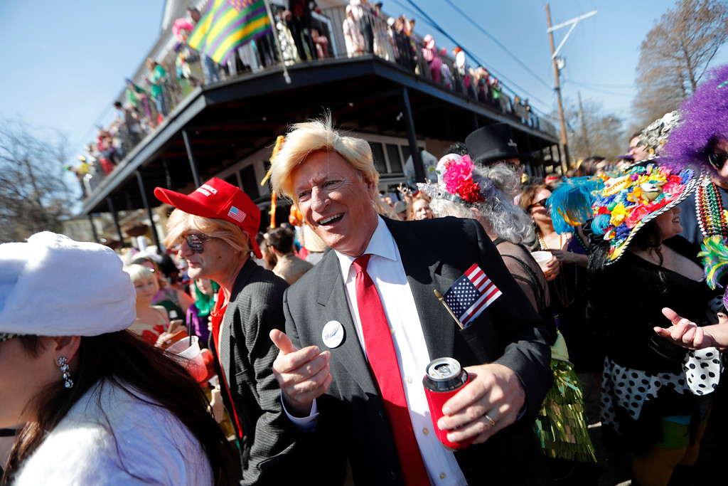 . John Shreves, center, of New Orleans, runs into Jeff Jones, right, who both dressed as Donald Trump, during the Society de Sainte Anne parade, on Mardi Gras day in New Orleans, Tuesday, Feb. 13, 2018. (AP Photo/Gerald Herbert)