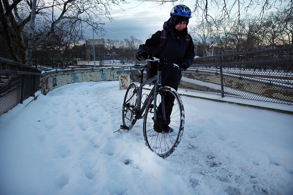 . A woman walks over a snow covered foot bridge with her bike in Brooklyn on the morning after a major winter storm blanketed much of New York City in 10 to 12 inches of snow on January 22, 2014 in New York City. While the storm caused major traffic and subway delays, New York City area schools were open on Wednesday morning.  (Photo by Spencer Platt/Getty Images)
