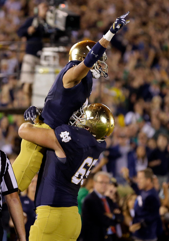 . Notre Dame wide receiver William Fuller, top, jumps into the arms of offensive linesman Conor Hanratty as he celebrates a touchdown against Michigan during the first half of an NCAA college football game in South Bend, Ind., Saturday, Sept. 6, 2014. (AP Photo/Michael Conroy)