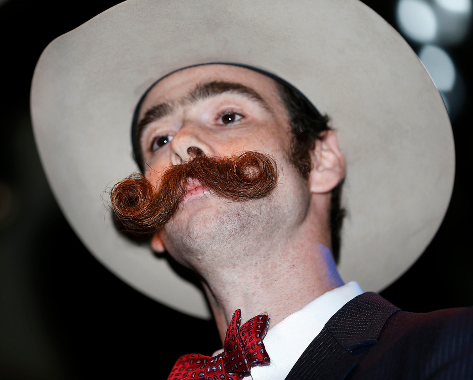 . Devon Holcombe of Jacksonville, Fla., poses for the crowd before continuing on to win a gold medal in the Natural Moustache division during the fourth annual Just For Men National Beard and Moustache Championships at The House of Blues Saturday, Sept. 7, 2013 in New Orleans. Contestants competed in 18 different categories including Dali, full beard natural and sideburns. (AP Photo/Susan Poag)