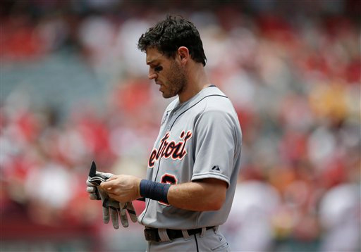 . Detroit Tigers\' Ian Kinsler takes off his gloves after the third inning of a baseball game against the Los Angeles Angels on Sunday, July 27, 2014, in Anaheim, Calif. (AP Photo/Jae C. Hong)