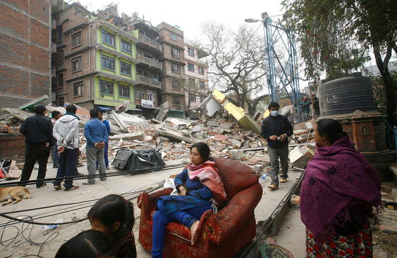 . A Nepalese woman sits on a sofa outdoors surrounded by the debris of Saturday\'s earthquake, in Kathmandu, Nepal, Sunday, April 26, 2015. Sleeping in the streets and shell-shocked, Nepalese cremated the dead and dug through rubble for the missing Sunday even as the worst of the aftershocks, magnitude 6.7, pummeled the capital city. (AP Photo/Bikram Rai)