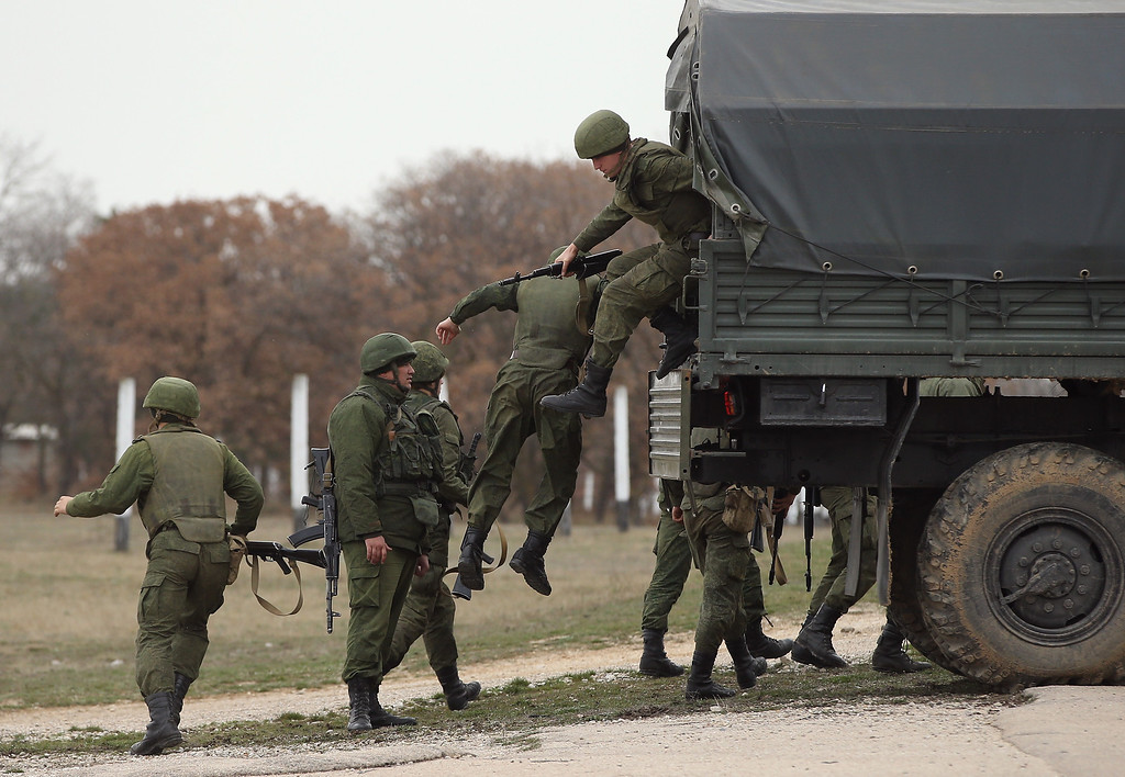 . LUBIMOVKA, UKRAINE - MARCH 04:  Troops under Russian command jump down from a truck with orders to shoot to kill anyone who advances further after over 100 unarmed Ukrainian troops confronted them at the Belbek airbase, which the Russian troops are occcupying, in Crimea on March 4, 2014 in Lubimovka, Ukraine. The Ukrainians are stationed at their garrison nearby, and after spending a tense night anticipating a Russian attack following the expiration of a Russian deadline to surrender, in which family members of troops spent the night at the garrison gate in support of the soldiers, their commander Colonel Yuli Mamchor announced his bold plan this morning to retake the airfield by confronting the Russian-lead soldiers unarmed. The Russian-lead troops fired their weapons into the air but then granted Mamchor the beginning of negotiations with their commander. Russian-lead troops have blockaded a number of Ukrainian military bases across Crimea.  (Photo by Sean Gallup/Getty Images)