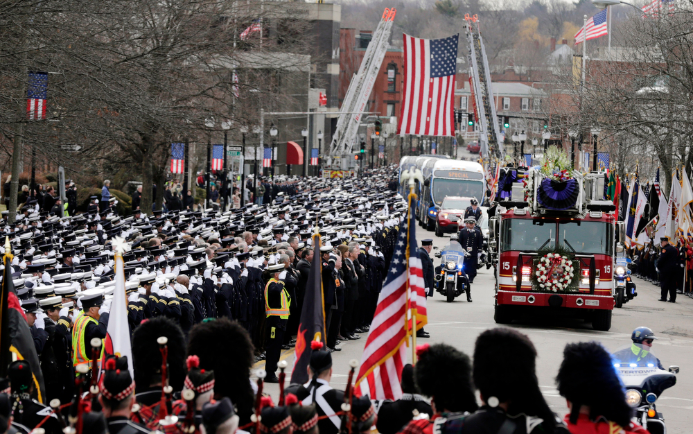Description of . Firefighters salute as the funeral procession for Boston fire Lt. Edward Walsh arrives outside St. Patrick's Church in Watertown, Mass., Wednesday, April 2, 2014. Walsh and his colleague Michael Kennedy died after being trapped while battling a nine-alarm apartment fire in Boston on March 26. (AP Photo/Charles Krupa)