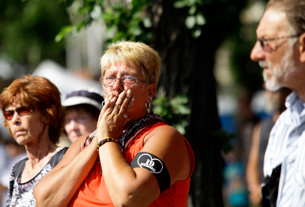 . A woman reacts, as hearses carrying the remains of the 19 members of the Granite Mountain Hotshot firefighting team who were killed fighting the Yarnell Fire, drive past in a motorcade from the Maricopa County Medical Examiner\'s office in Phoenix, Arizona July 7, 2013. A solemn procession of 19 white hearses carrying the remains of firefighters killed battling an Arizona wildfire left Phoenix accompanied by police motorcycle outriders on Sunday on a final journey passing through the crew\'s hometown.REUTERS/Joshua Lott
