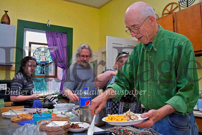 Bob Madjaric(right) and members of the Ginger Hill Unitarian Universalist Congregation prepare plates at their bimonthly potluck. Seb Foltz/Butler Eagle