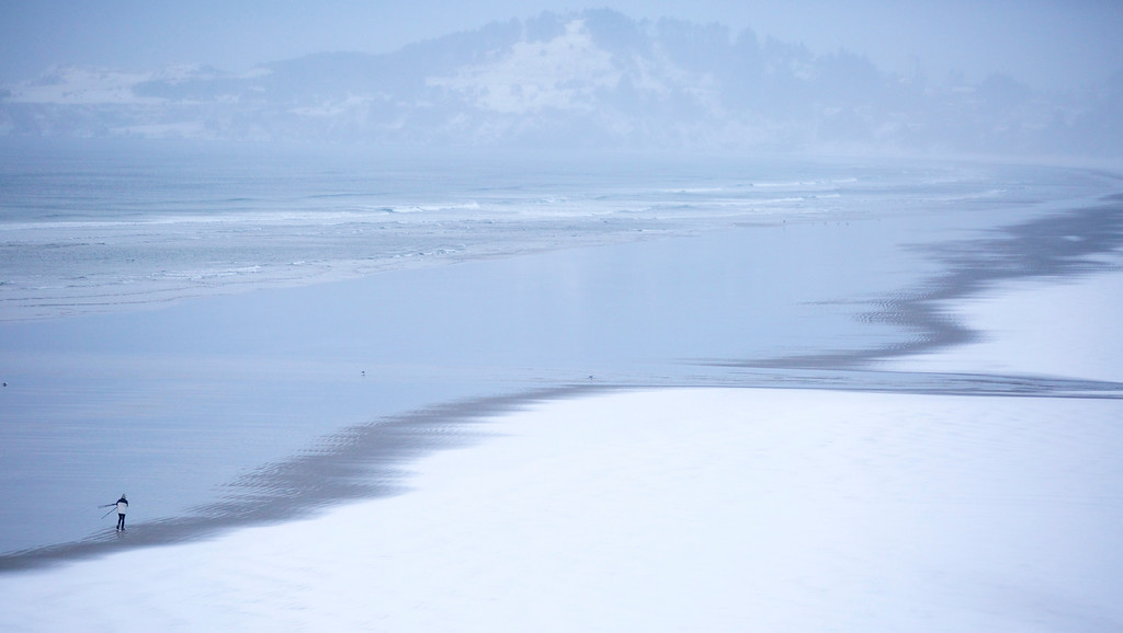 . A photographer walks on the beach after a winter storm delivered snow overnight Friday, Dec. 6, 2013, in Newport, Ore. Forecasters expect up to 3 inches of snow on the Oregon coast and up to 10 inches east of the Cascade Range. (AP Photo/The Oregonian, Randy L. Rasmussen)