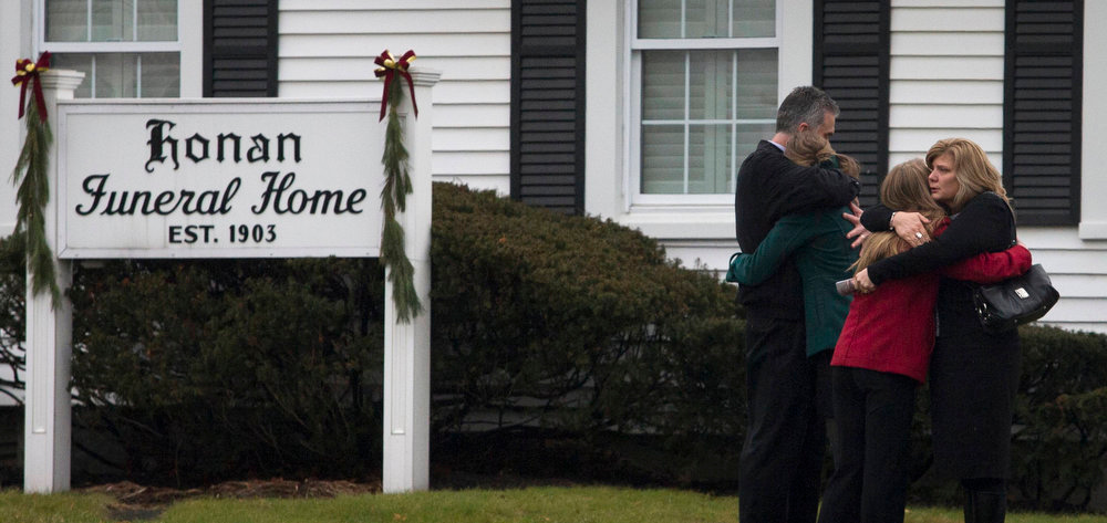 Description of . Mourners embrace outside a funeral home where services for six-year-old Jack Pinto, one of 20 schoolchildren killed in the December 14 shootings at Sandy Hook Elementary School, was being held in Newtown, Connecticut December 17, 2012. The two funerals on Monday ushered in what will be a week of memorial services and burials for the 20 children and six adults massacred at Sandy Hook Elementary School in Newtown, Connecticut. REUTERS/Adrees Latif