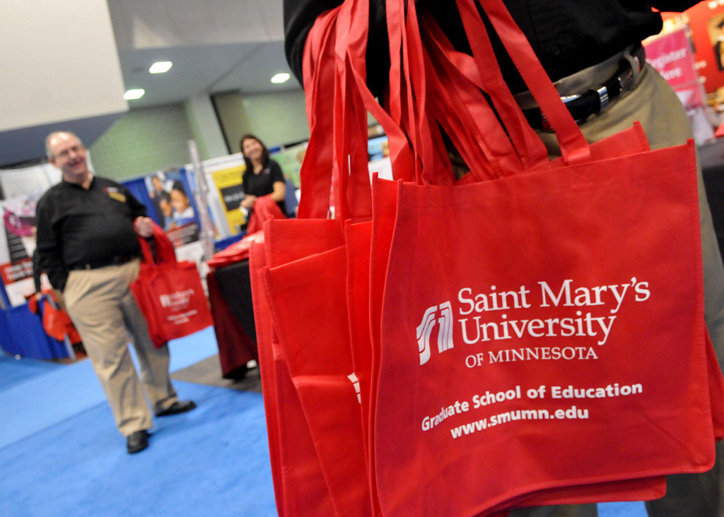 . Craig Sundberg, right, a Program Director in Educational Leadership at St. Mary\'s University, hands out tote bags, which were in big demand for carrying all the handouts available at the conference. (Pioneer Press: John Doman)