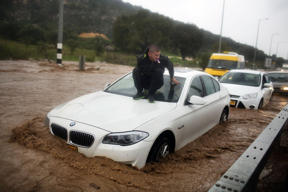Description of . A man sits on top of his car which is stuck in a flooded road near the Israeli-Arab town of Kfar Qara, in central Israel, on January 8, 2013. Stormy weather, including high winds and heavy rainfall, lashed Israel and the Palestinian territories, downing powerlines and trees and  blocking roads causing several injuries. MENAHEM KAHANA/AFP/Getty Images