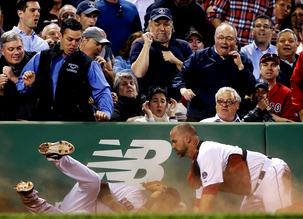 . Fans react as Boston Red Sox third baseman Will Middlebrooks, left, crashes into catcher David Ross while making the play on a pop foul by Minnesota Twins\' Chris Parmelee during the fifth inning of a baseball game at Fenway Park in Boston, Tuesday, May 7, 2013. Middlebrooks made the catch for the out. (AP Photo/Elise Amendola)