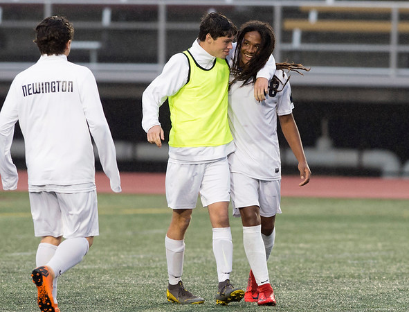 10/29/19 Wesley Bunnell | StaffrrNew Britain soccer was defeated 2-0 by Newington during a drizzle at Veterans Stadium on Tuesday afternoon. Mannasah Dalomba (18) is greeted by teammates at the conclusion of the game.