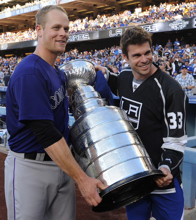 . Rockies Justin Morneau, who wears a #33 on his back, poses for a photo with the cup and Kings#33 Willie Mitchell. Members of the Los Angeles Kings brought the Stanley Cup to Dodger Stadium for photographs before the Dodgers played the Colorado Rockies.  Los Angeles, CA. 6/18/2014(Photo by John McCoy Daily News)