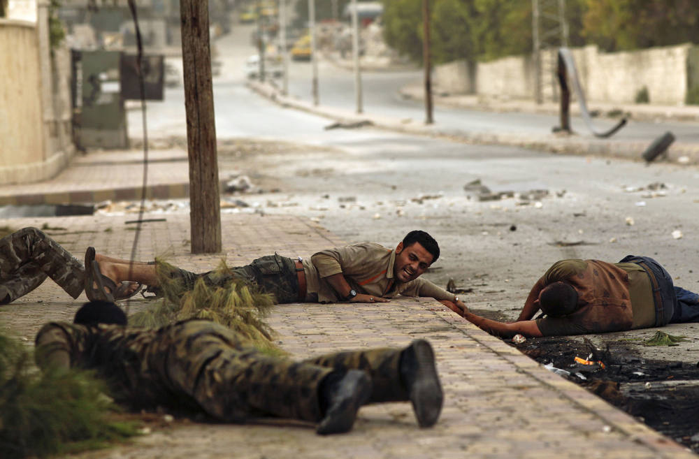 Description of . Members of the Al-Baraa bin Malek battalion, part of the Free Syria Army's Al-Fatah brigade, duck to the ground as they pull a man (R) who was shot by a sniper twice in the Bustan al-Basha district of the northern city of Aleppo on October 20, 2012. Due to the risk of being shot by the sniper, no one was able to rescue the man who eventually ran towards rebels, only to be shot by the sniper a second time. Rebels then pulled him and rushed him to a hospital, though it is not known if he survived. Three civilians were shot on this main road in the space of three hours by the same sniper. AFP PHOTO/JAVIER  Manzano/AFP/Getty Images