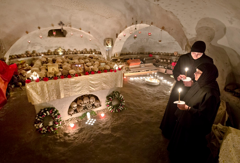 . Romanian orthodox nuns hold candles in the ossuary at the Pasarea monastery, outside Bucharest, Romania, Sunday, May 5,  2013, after the Easter Religious service. The ossuary, containing mostly remains of the nuns that lived at the monastery is briefly opened on Easter night.(AP Photo/Vadim Ghirda)