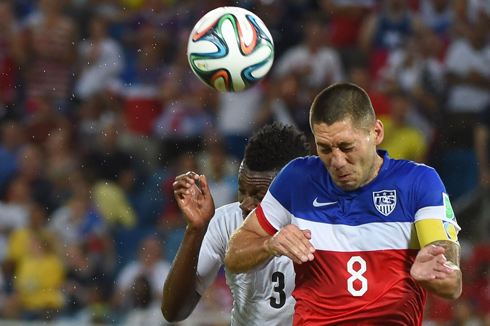 Description of . US forward Clint Dempsey (R) and Ghana's forward Asamoah Gyan (L) jump for the ball during a Group G football match between Ghana and US at the Dunas Arena in Natal during the 2014 FIFA World Cup on June 16, 2014.  AFP PHOTO / EMMANUEL DUNANDEMMANUEL DUNAND/AFP/Getty Images