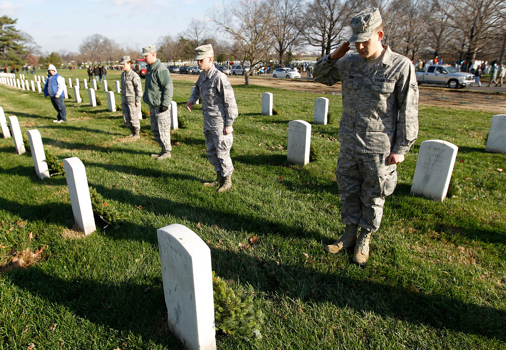 . Airman Michael Kern, right, salutes over the grave of a fallen soldier after placing holiday wreaths at the graves of fallen soldiers during Wreaths Across America Day  at Arlington National Cemetery on Saturday Dec. 10, 2011. (AP Photo/Jose Luis Magana)
