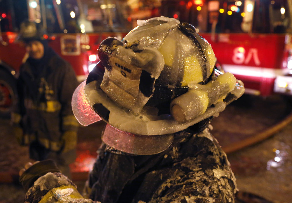 Description of . A Chicago firefighter's helmet is covered with ice from single digit temperatures during a five-alarm blaze in a warehouse on the city's South Side, Bridgeport neighborhood Wednesday, Jan. 23, 2013, in Chicago. (AP Photo/Charles Rex Arbogast)