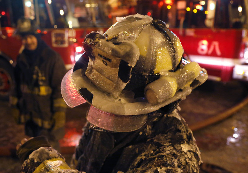 . A Chicago firefighter\'s helmet is covered with ice from single digit temperatures during a five-alarm blaze in a warehouse on the city\'s South Side, Bridgeport neighborhood Wednesday, Jan. 23, 2013, in Chicago. (AP Photo/Charles Rex Arbogast)